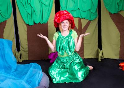 Aktorka na scenie ubrana w zielony strój i czerwony kapelusz