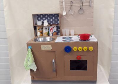 szafka kuchenna zbudowana z odpadów postawiona na białym obrusie
