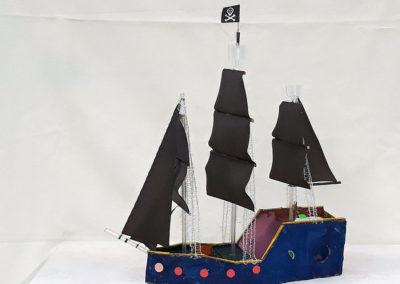piracki statek zbudowany z odpadów postawiony na białym obrusie