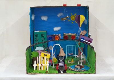 domek oraz plac zabaw zbudowane z odpadów postawione na białym stoliku