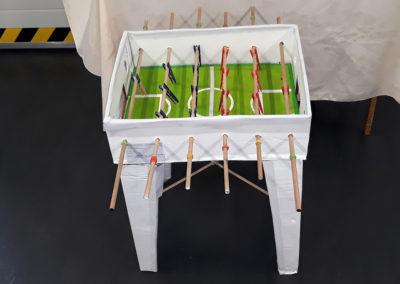 stolik do gry w piłkarzyki zbudowany z odpadów postawiony na czarnej podłodze