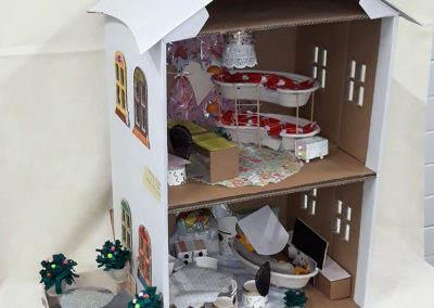piętrowy domek i ogródek zbudowane z odpadów postawione na białym obrusie