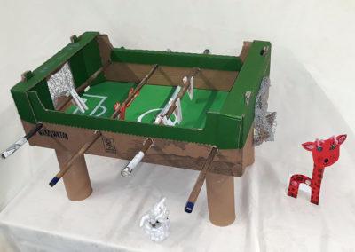 gra piłkarzyki zbudowana z odpadów i postawiona na białym obrusie