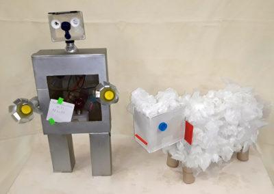 robot i zwierzę zbudowane z odpadów stojące na białym obrusie