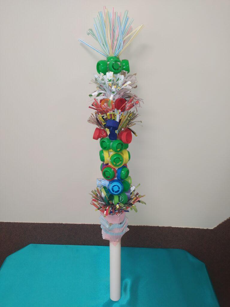kolorowa palma wielkanocna zbudowana z nakrętek i plastikowych słomek na beżowym tle